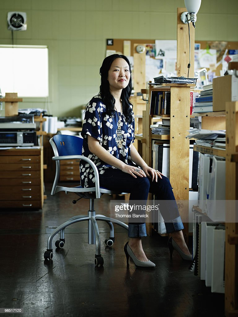 Businesswoman seated in office chair smiling : Stock Photo