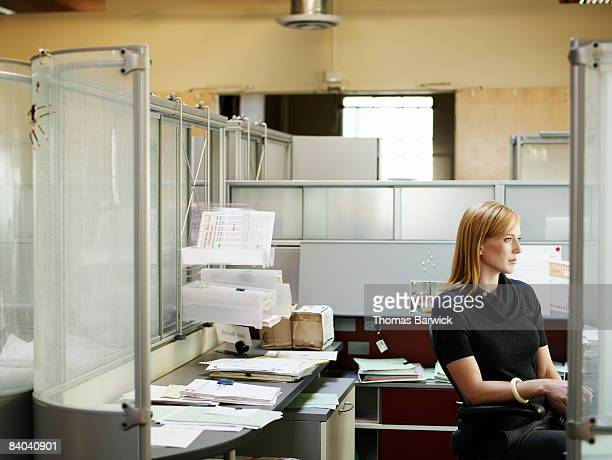 Businesswoman seated in office cubicle