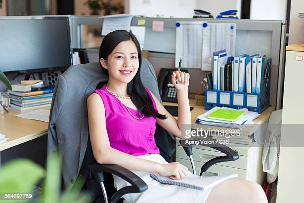 businesswoman seated in office workstation