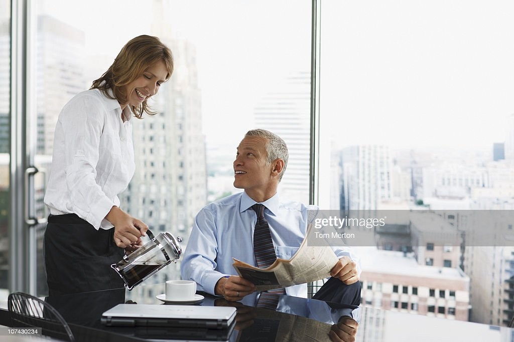 Businesswoman serving co-worker coffee in office