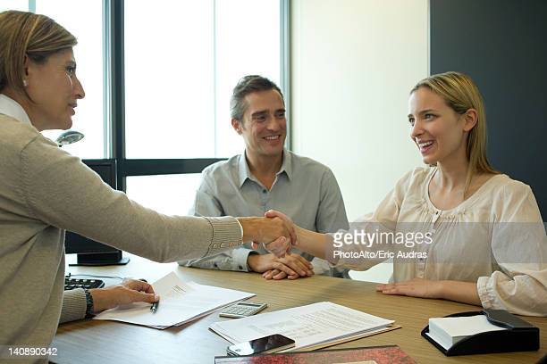 Businesswoman shaking hands with client in office