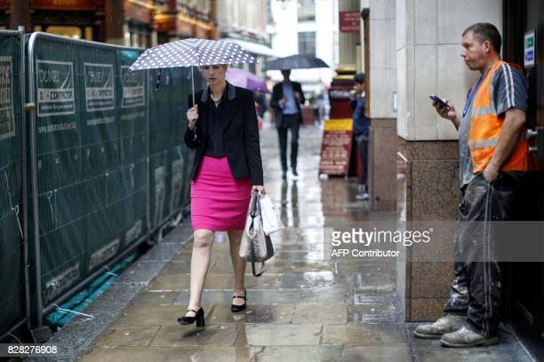 A businesswoman shelters from the rain beneath an umbrella as she passes a construction worker near Leadenhall Market in London on August 9 2017...