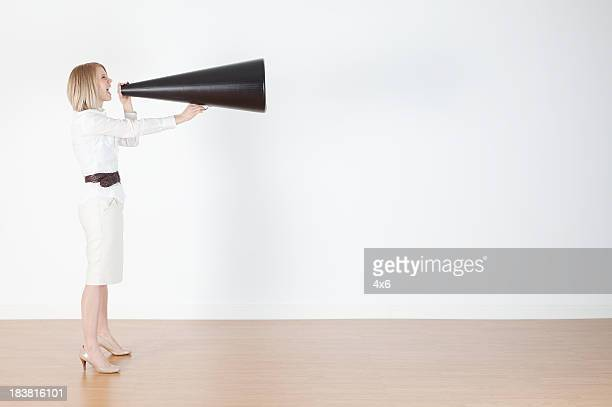 Businesswoman shouting into a bullhorn