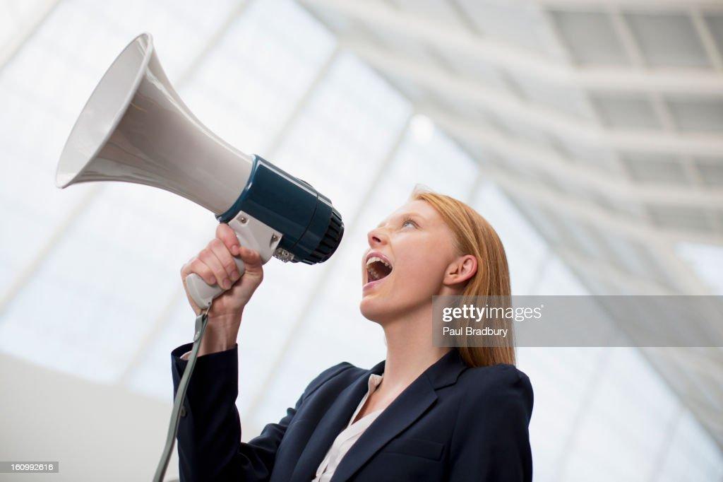 Businesswoman shouting into bullhorn