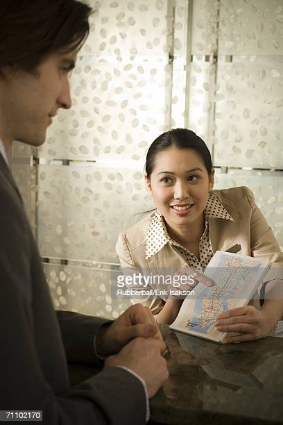 Businesswoman showing a map to a businessman