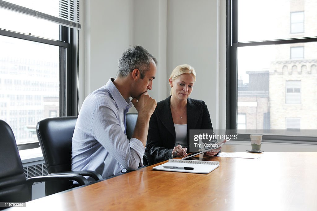 Businesswoman showing colleague digital tablet : Stock Photo