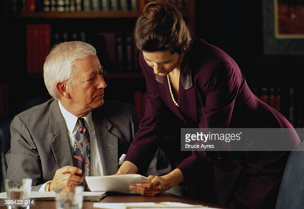 Businesswoman showing document to mature male executive at table