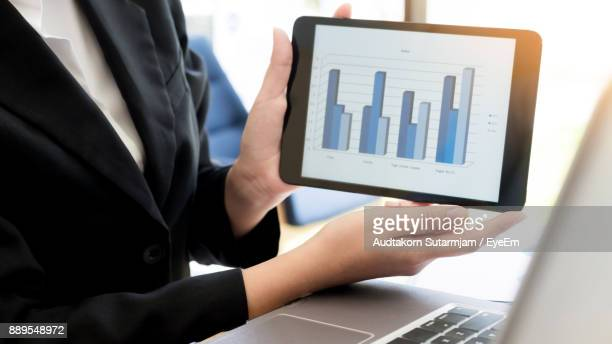 Businesswoman Showing Graph On Digital Tablet At Office