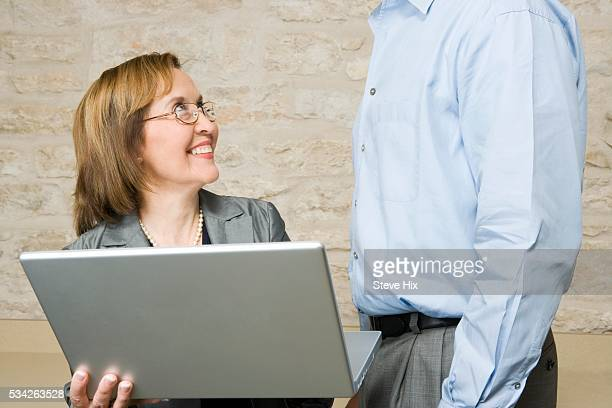 Businesswoman Showing Laptop to Businessman