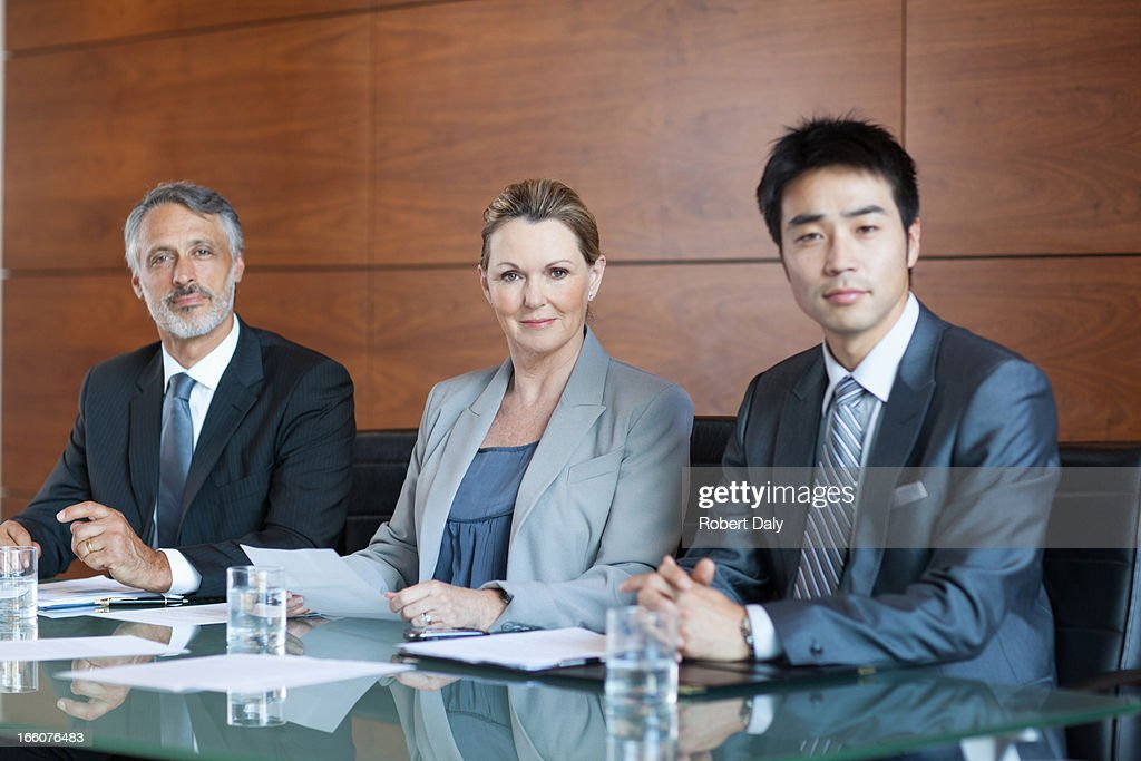 Businesswoman showing paperwork to businessmen in meeting : Stock Photo