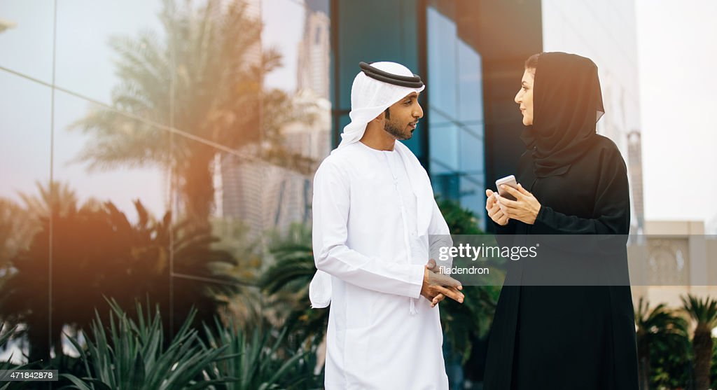 Businesswoman showing something to emirati businessman