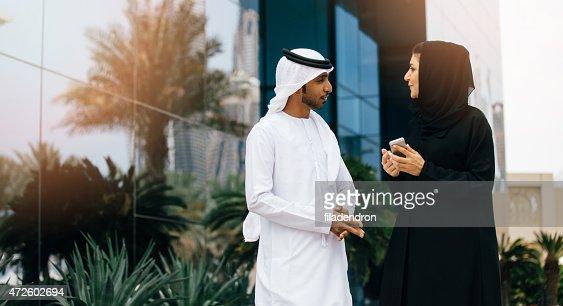 Businesswoman showing something to emirati businessman