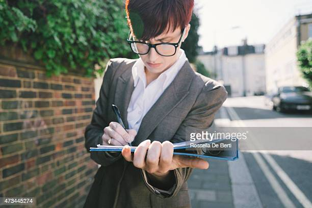 A businesswoman signing documents in a quiet street