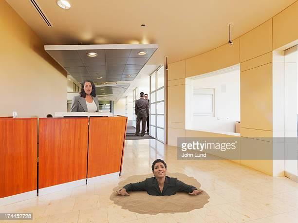Businesswoman Sinking In Office Quicksand