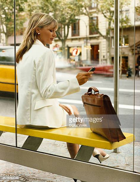 Businesswoman Sits at a Bus Stop Using Her Mobile Phone