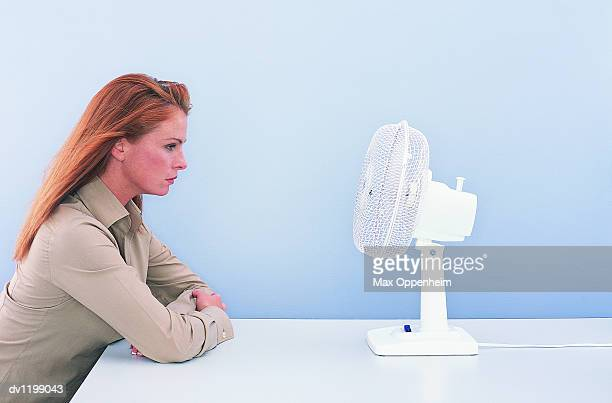 Businesswoman Sitting at a Table by an Electric Fan