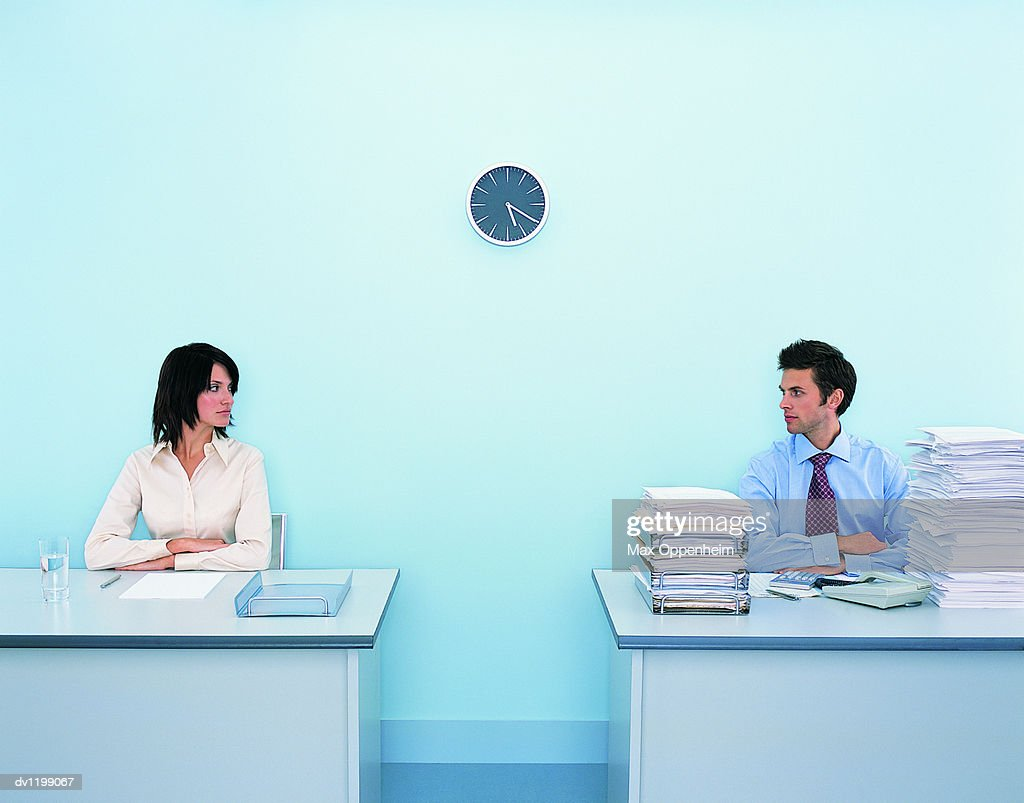 Businesswoman Sitting at a Tidy Desk Looking Sideways at a Businessman Sitting at a Messy Desk : Stock Photo