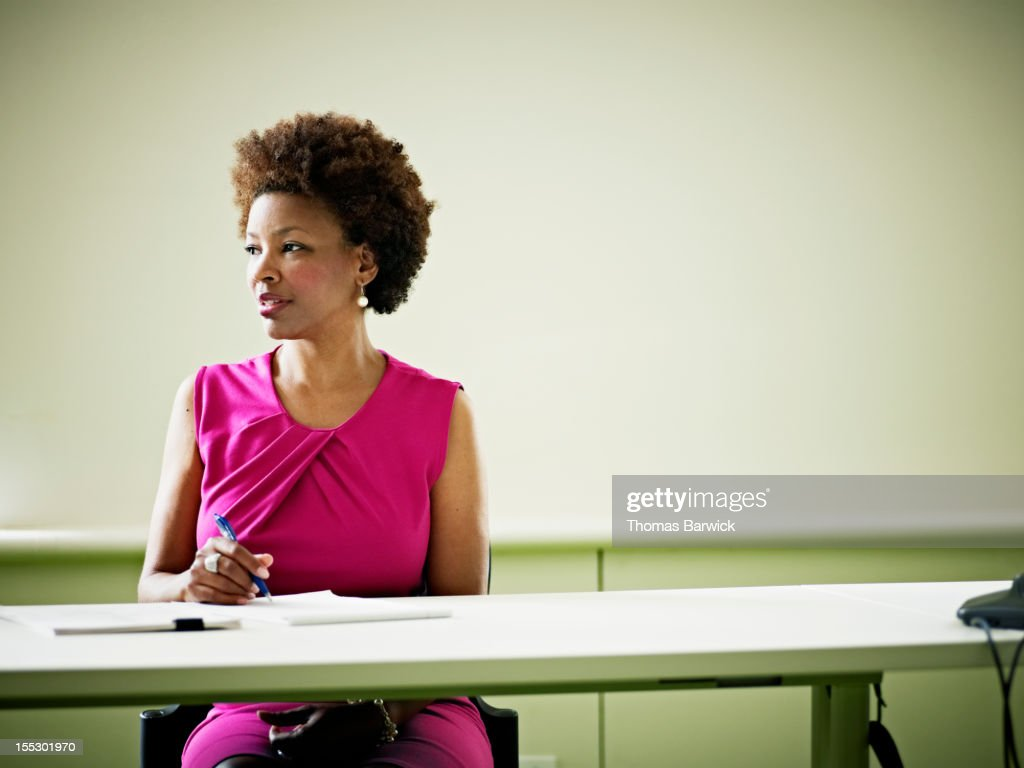 Businesswoman sitting at conference room table : Stock Photo