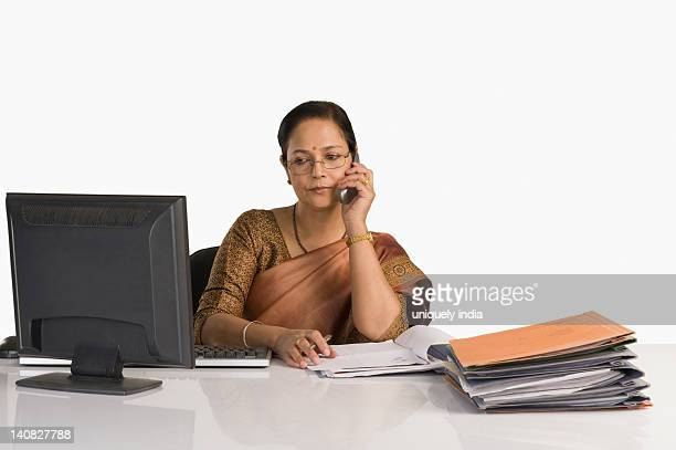Businesswoman sitting at desk and talking on a mobile phone