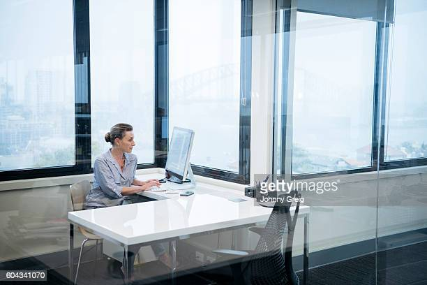 Businesswoman sitting at desk behind glass in modern office