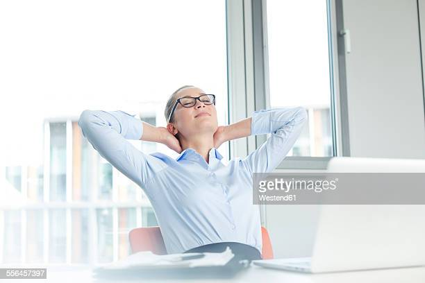 Businesswoman sitting at desk, day dreaming
