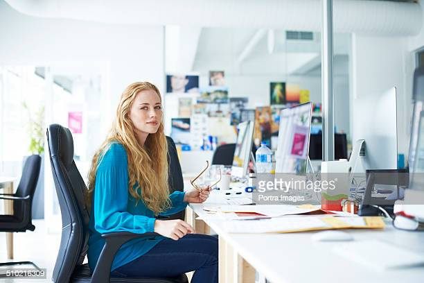 Businesswoman sitting at desk in creative office