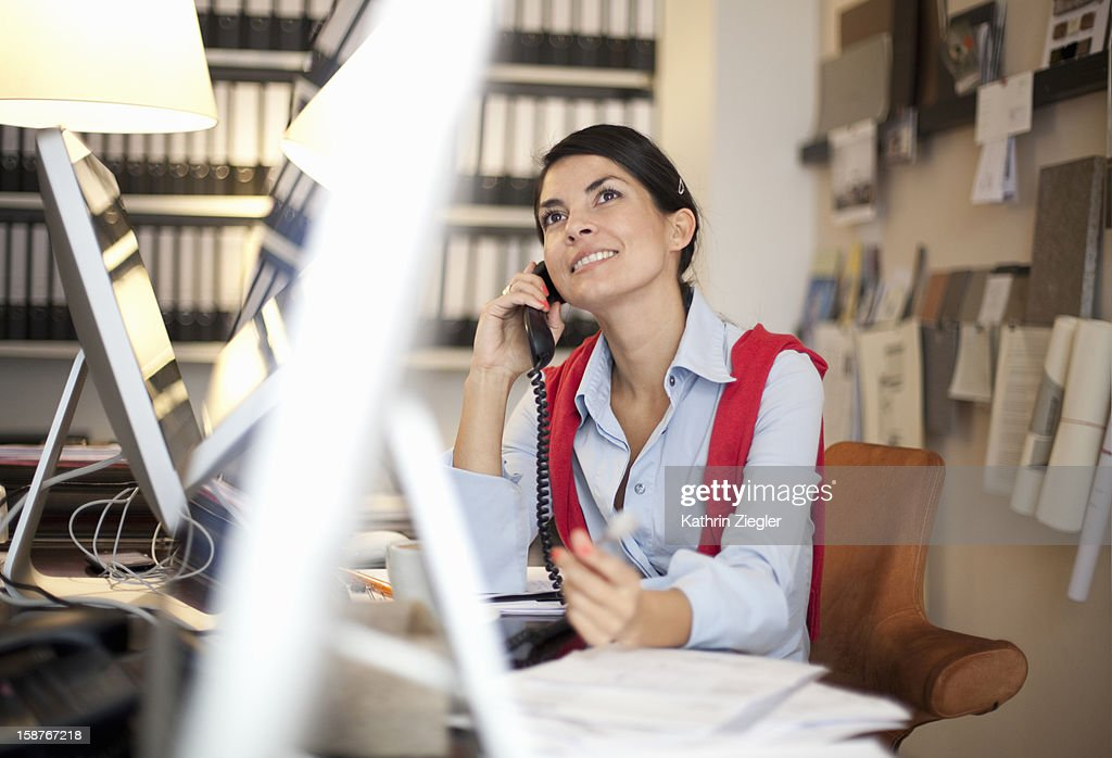businesswoman sitting at desk in office : Stock Photo