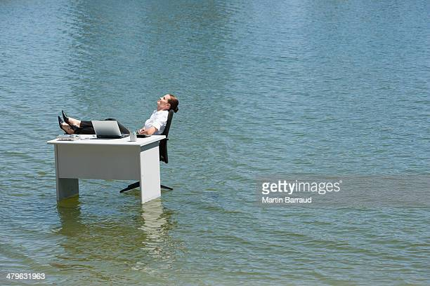 Businesswoman sitting at desk in water