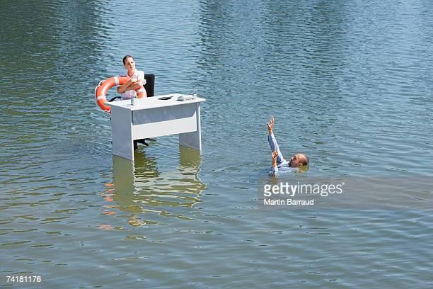 Empresaria sentado en el escritorio de agua con dispositivo de flotación y