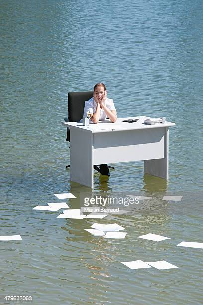Businesswoman sitting at desk in water with paperwork floating away