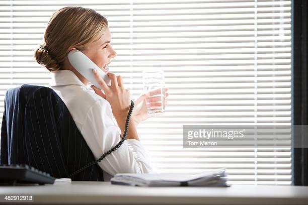 Geschäftsfrau Sitzen am Schreibtisch sprechen am Telefon