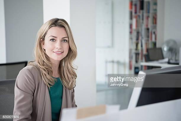 Geschäftsfrau Sitzen am Schreibtisch mit Computer und Lächeln in die Kamera