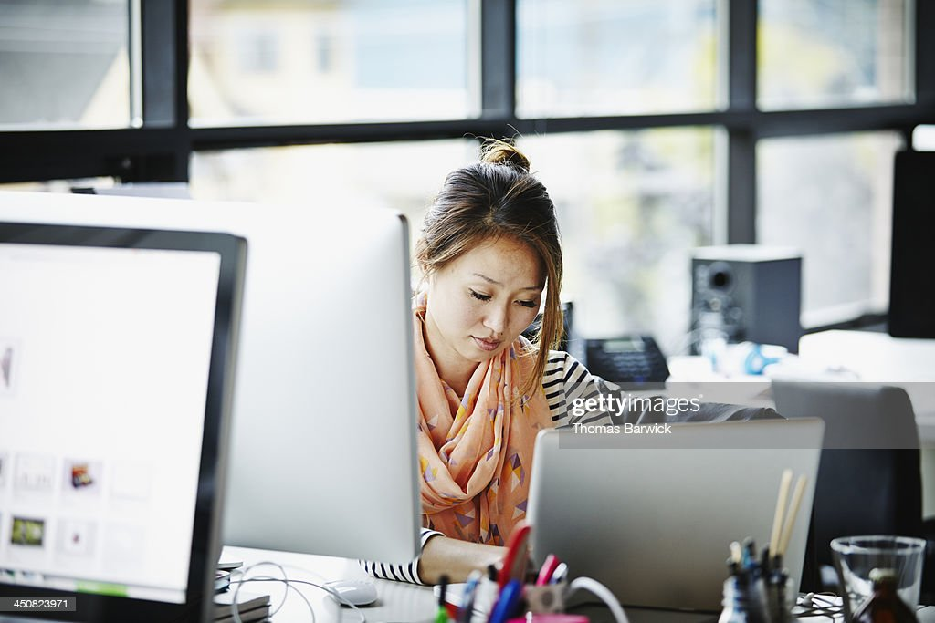 Businesswoman sitting at desk working on laptop : Stock Photo