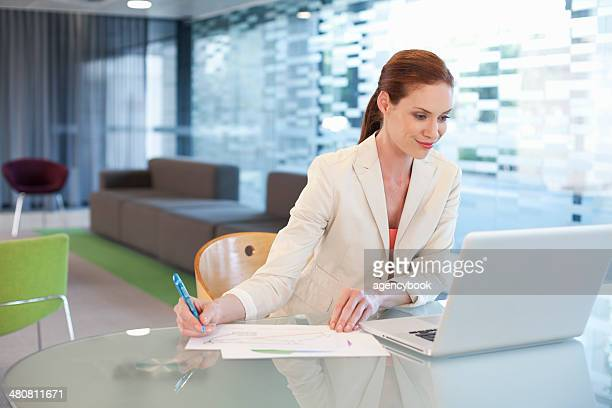 Businesswoman sitting at desk, writing activity