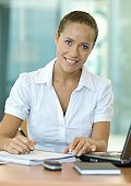 Businesswoman sitting at desk, writing, smiling at camera