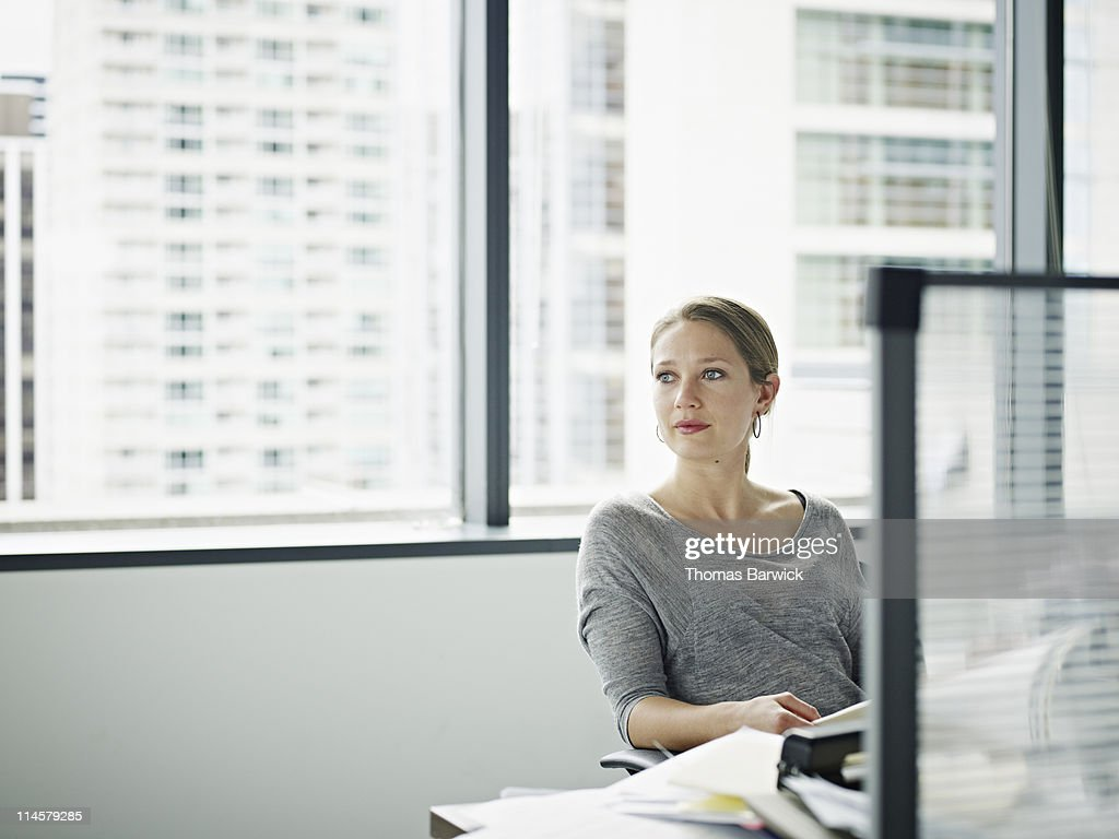 Businesswoman sitting at messy desk looking out : Stock Photo