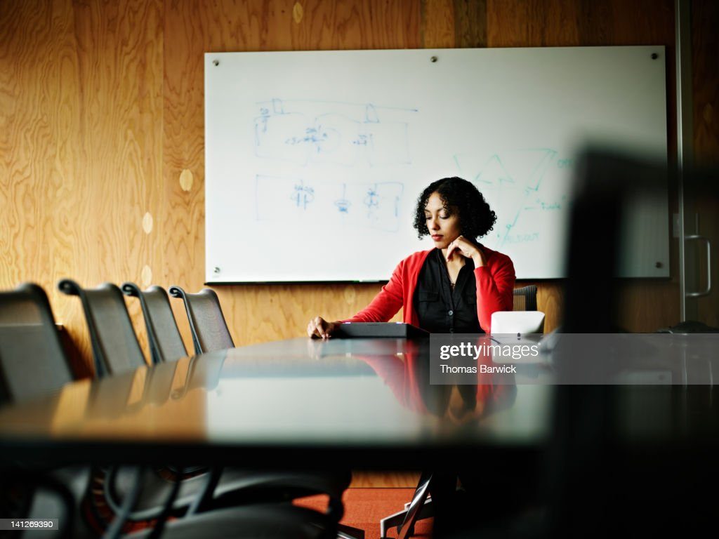 Businesswoman sitting at office conference table : Stock Photo