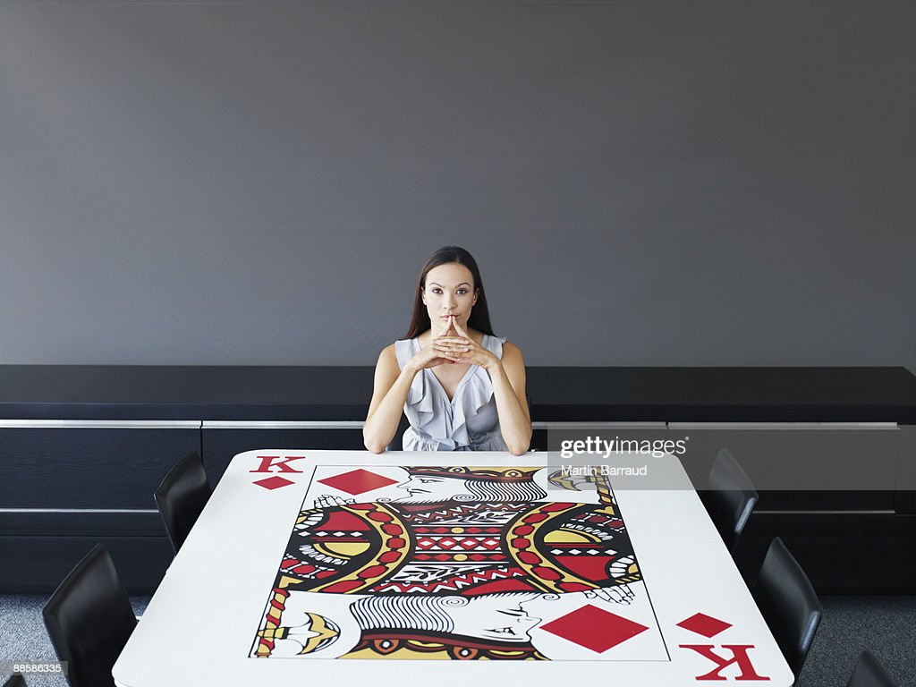Businesswoman sitting at playing card conference table