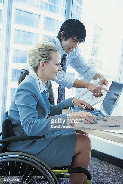 Businesswoman Sitting in a Wheelchair Being Trained on a Laptop by a Businessman