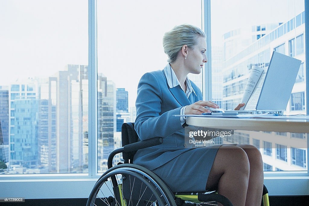 Businesswoman Sitting in a Wheelchair Working on a Laptop in the Office