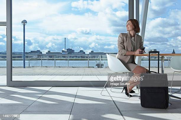 Businesswoman sitting in airport with suitcase