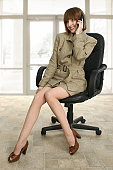 Businesswoman sitting in an office chair and talking on a mobile phone