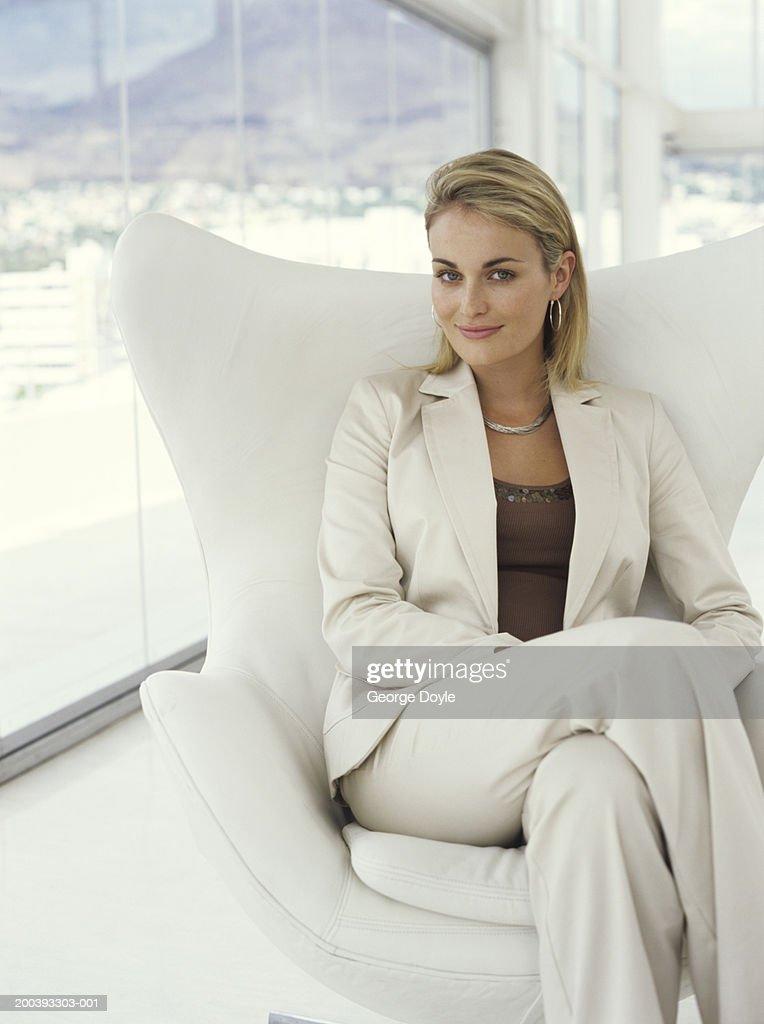 Businesswoman sitting in armchair, portrait : Stock Photo
