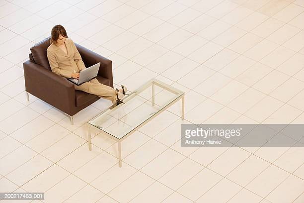 Businesswoman sitting in armchair using laptop, with feet up on table