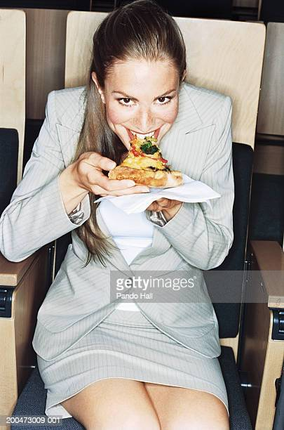 Businesswoman sitting in auditorium, eating pizza, smiling, portrait