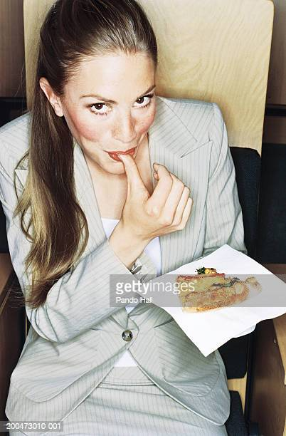 Businesswoman sitting in auditorium, holding pizza, smiling, portrait