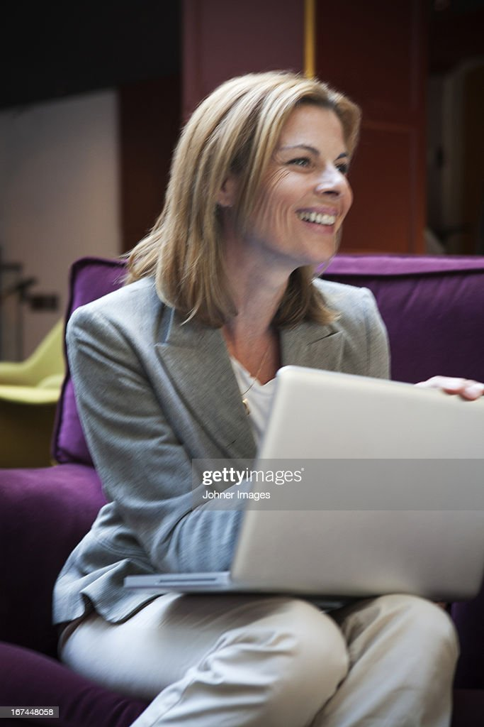 Businesswoman sitting in cafe and using laptop : Stock Photo