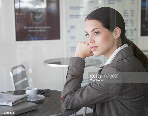 Businesswoman sitting in cafeteria with laptop looking out window