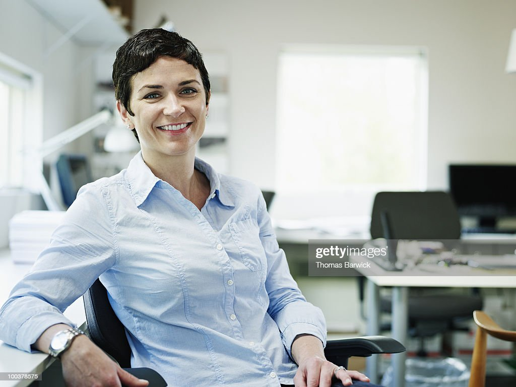 Businesswoman sitting in chair in office smiling : Stock Photo