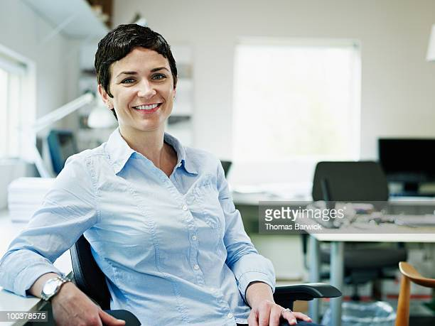 Businesswoman sitting in chair in office smiling